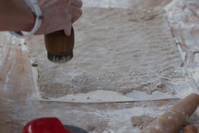 Stamping the rye crackers with Middle Eastern bread stamps before being baked in the wood-fired oven.